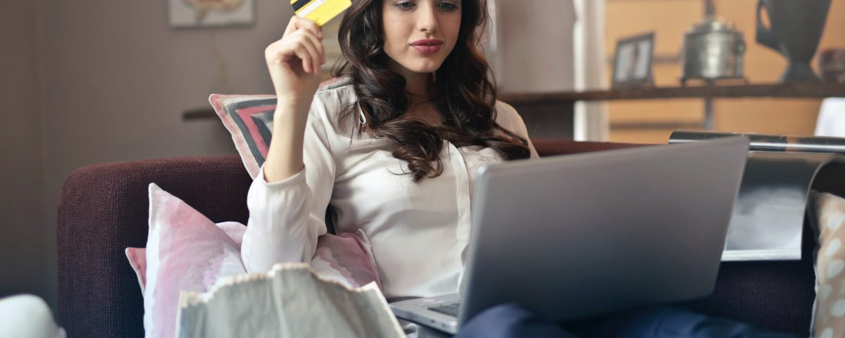 woman using credit card at home on laptop